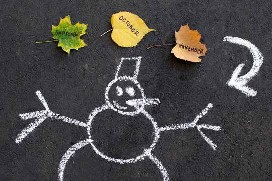 Chalk Drawing snowman on black asphalt. brown, green, yellow leaves trees with the inscription word September, October, November. Winter is coming, change of seasons, concept.