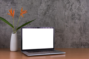 Blank screen of laptop computer with flowers vase on raw concrete background