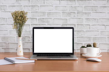 Blank screen of laptop computer with coffee cup, dry flowers, note book, pencil and cactus vase on white bricks background