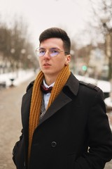 Young man smiling with a urban look in city. hipster man in the city winter