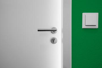 offene Tür mit Lichspalt und grüner Wand