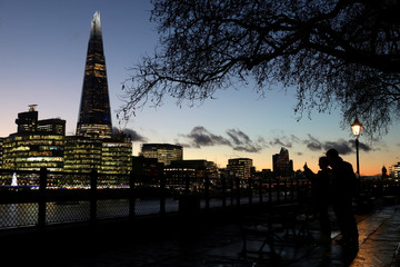 People walk alongside the Thames as the sun sets behind The Shard in London