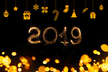 New Year 2019. Sparks of Bengal 2019 on a black background with gold bokeh lights and holiday decorations.