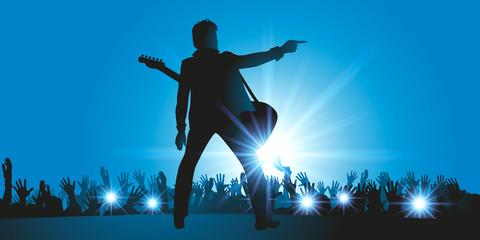 dans une salle de concert, une star du rock fait son show et chante sur scène devant une foule de fans en délire
