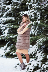 Winter portrait: Young pretty woman dressed in a warm woolen clothes posing outside.