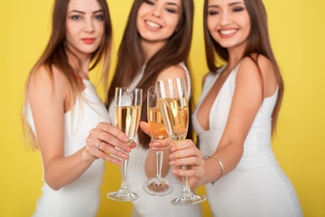 Three young woman in elegant dresses having fun, smiling, dancing and drinking champagne on yellow background. Christmas party celebration concept.
