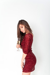 Beautiful brunette woman wearing elegant red dress holding a glass of champagne in her hand on white background