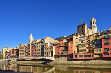 colorful houses facing the river Onyar and Catathedral and Sant Feliu Church, Girona, Catalonia, Spain