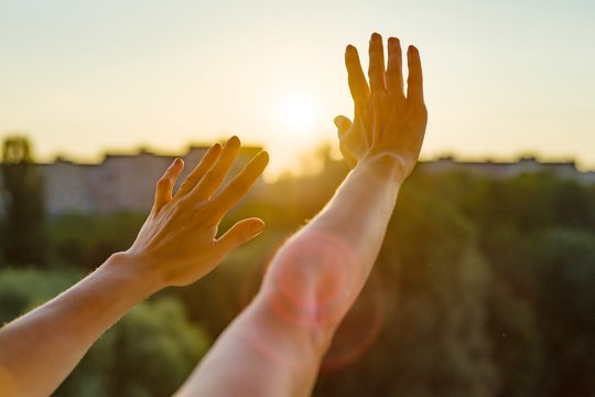 Hands open to the sunset, meditation, religion, prayer, background of the open window in the house, the silhouette of the city and the evening sun