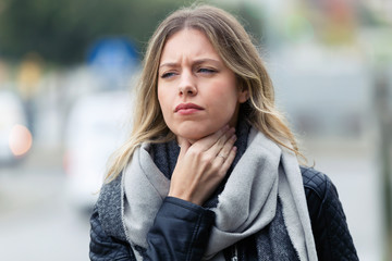 Illness young woman with terrible throat pain walking to the street.