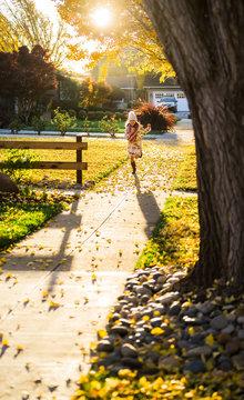 Girl running on walkway between yellow leaves