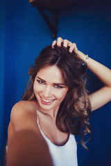 Pleasant girl making selfie in studio and laughing. Good-looking young woman taking picture of herself on blue background.