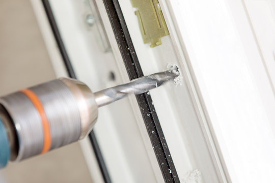 Close up boring hole with cutting tool during PVC window or door installation