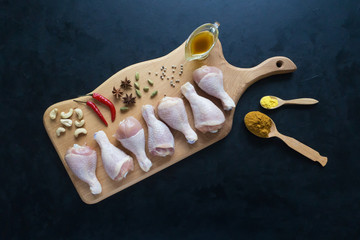 Chicken legs with spices on a wooden board.