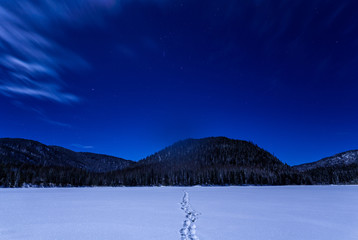 Fototapete - Footprints On Snowy Lake At Night