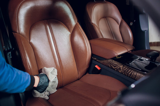 Auto service staff cleaning car interior detailing and valeting concept