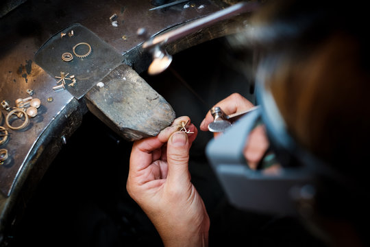 Jeweler saws at a gold ring in authentic jewellery workshop
