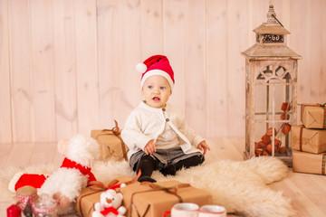 Baby in Santa hat in bright Christmas interior.