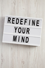 'Redefine your mind' words on lightbox over white wooden surface, top view. Overhead, flat lay, from above.