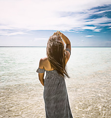 Beautiful young woman with a nice dress looking at the ocean with crystal clear water and sky with her hands gliding through her hair.