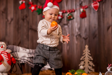 Christmas photo of the baby on a dark background of a wooden house, the baby next to the sled holds a tangerine.