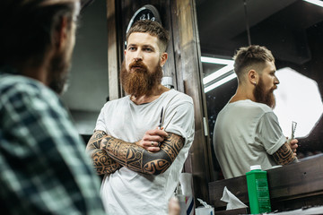 Waist up of thoughtful barber standing with crossed arms and looking