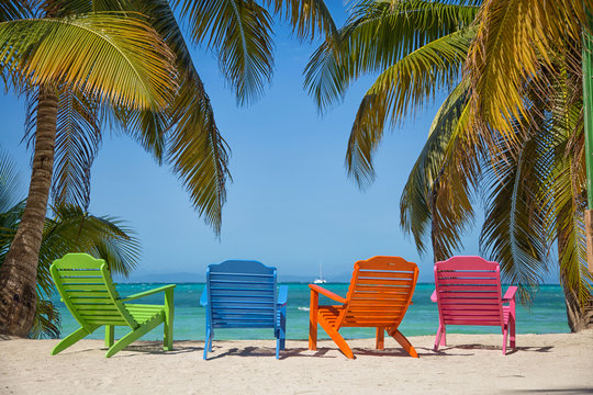 A tropical beach island with beautiful sand and turquoise water with palm trees. It the South Water Caye island in Belize and it's a typical Caribbean island.