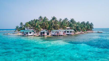Photo sur Toile Ile Aerial drone view of Tobacco Caye small Caribbean island with palm trees and bungalows in the Belize Barrier Reef