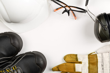 Work safety and protection equipment - protective shoes, safety glasses, gloves and hearing protection over white Wall mural