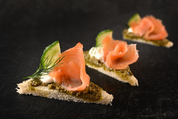 canapes in a row with smoked salmon, cucumber, pesto and dill garnish on dark stone with copy space, close up