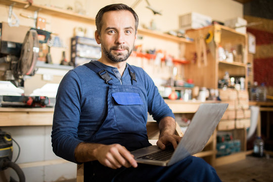 Portrait of mature worker using laptop and looking at camera in workshop interior, copy space