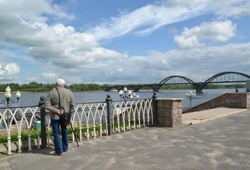 The elderly person on costs on Volzhskaya Embankment and looks at Volga. Rybinsk, Yaroslavl region