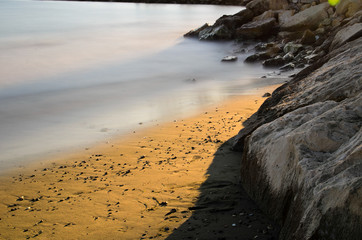 A shot of the sea, the golden sand and the sun hitting only the middle of the   scene