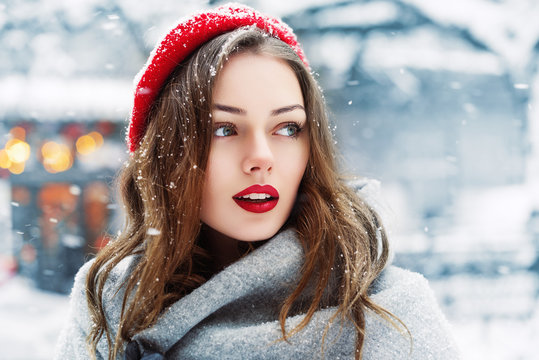 Outdoor close up portrait of young beautiful fashionable woman with red lips,  wearing woolen beret, scarf, posing in street of european city. Winter fashion, Christmas holidays concept. Copy space
