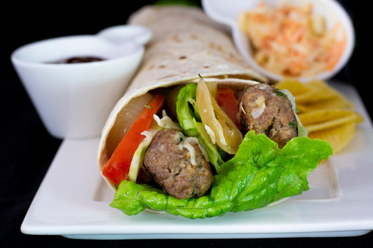 Delicious meatball wrap with salad inside with isolated black background
