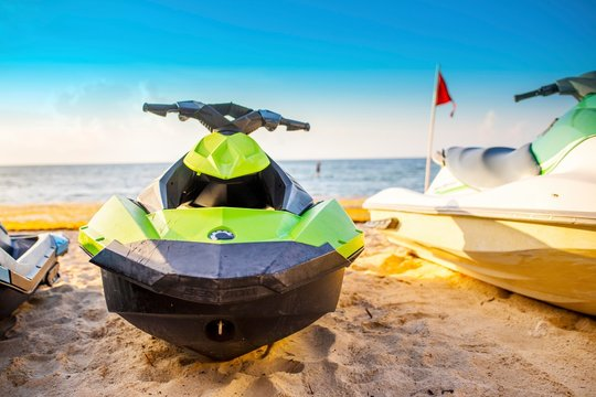 Jet ski front view parked on a white sandy Caribbean beach on the Riviera Maya, available to hire for water sports on the ocean