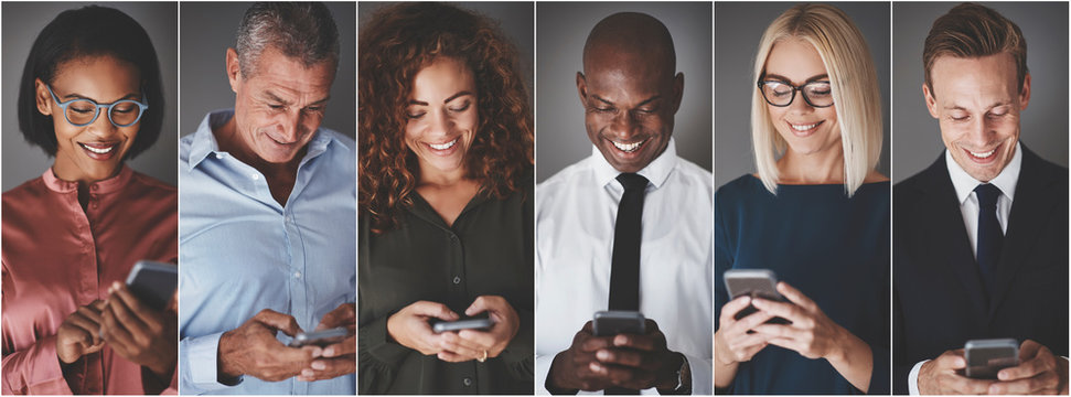 Smiling group of diverse businesspeople sending text messages