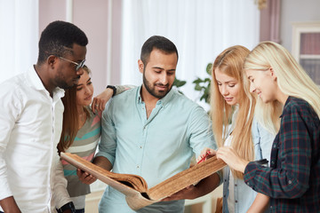 Handsome Arabian young bearded man surrounded by multiracial male and female students holding in hands big ancient book in library