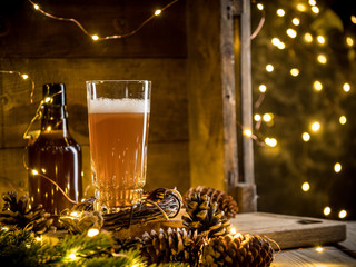 Photo sur Aluminium Biere, Cidre Beer in glass on wooden background with Christmas lights and pine cones