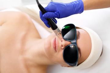 Fotoodmładzanie za pomocą lasera. Kobieta w salonie kosmetycznym podczas zabiegu z użyciem lasera.