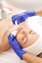 Kosmetyczka oczyszcza skórę kobiety. Oczyszczanie skóry twarzy, kosmetyczka wyciska zaskórniki.