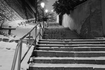 """Snow covered stairs in old town of Prague, Czech Republic. Stairs in """"Novy Svet"""" district illuminated by vintage street lamps. Monochrome night image"""