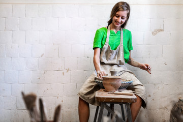Positive rejoice beautiful attractive lady artist her workwear she sit inside workspace studio create best product foe sale used circular wheel make handicraft dishes tableware copy space for text
