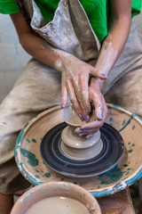 Vertical high angle above top view lady in her workwear she sit inside workspace transform piece of mud in beautiful small tea cup by hands