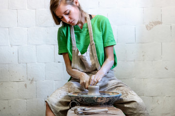Beautiful attractive pretty dreamy concentrated confident calm lady in her workwear she look down sit inside workspace make craft clay product by hands against white brick wall background
