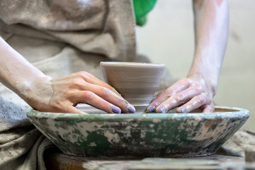 Master class concept. Cropped close up photo of workmanship lady in her dirty workwear she sit inside workspace using circular ceramics wheel made small cup