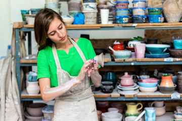 Master class concept. Gorgeous nice adorable good-looking lady in her casual green t-shirt workwear she stand indoor workspace against wooden shelf with utensil stuff background with clay cup in hand