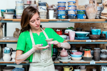 Master class concept. Beautiful attractive dreamy charming nice lady in her workwear she stand against wooden shelf with utensil stuff background inside workspace studio check quality of ceramics cup