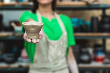 Blurred confident lady in her casual green t-shirt workwear she stand against wooden shelf inside workspace show on camera small ceramics cup in hand focus on front object copy space for text