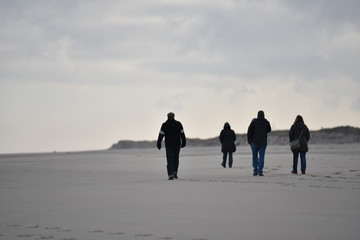 people walking at the beach in winter time